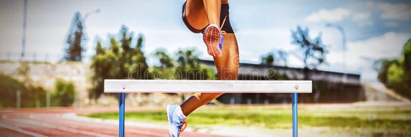 Żeńskiej atlety doskakiwanie nad przeszkoda zdjęcie royalty free