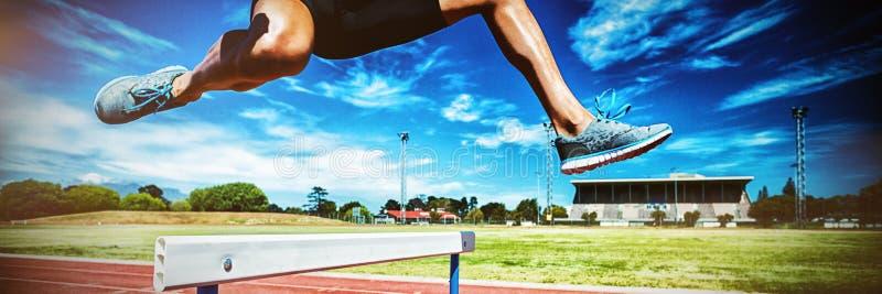 Żeńskiej atlety doskakiwanie nad przeszkoda obraz stock