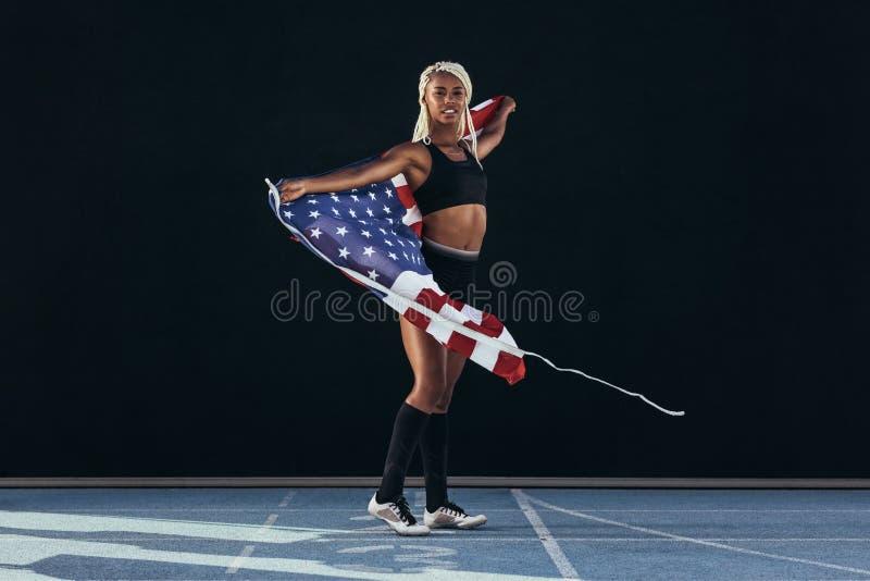 Żeńskiej atlety odprowadzenie na bieg śladu mienia flaga amerykańskiej obrazy royalty free
