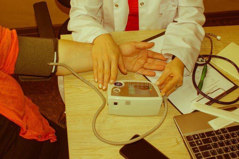Żeńskiej medycyny lekarki pomiarowy ciśnienie krwi pacjent podczas gdy gawędzący ona Kobieta komunikuje z lekarzem podczas medycz zdjęcia royalty free