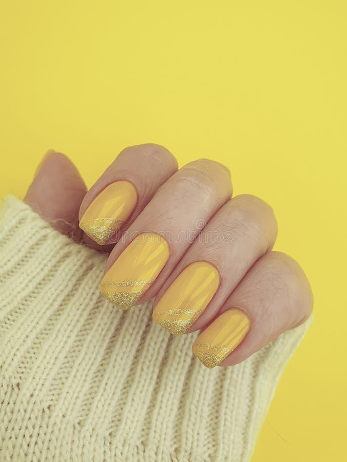Żeńskiej ręki manicure'u puloweru żółta zima obraz royalty free