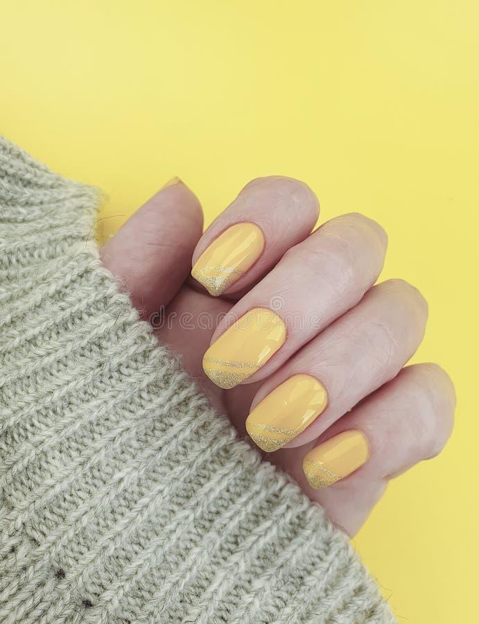 Żeńskiej ręki manicure'u puloweru zimy żółta dekoracja fotografia royalty free