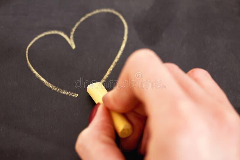 Żeńskiej Ręki Rysunkowy Serce Na Blackboard Obrazy Stock