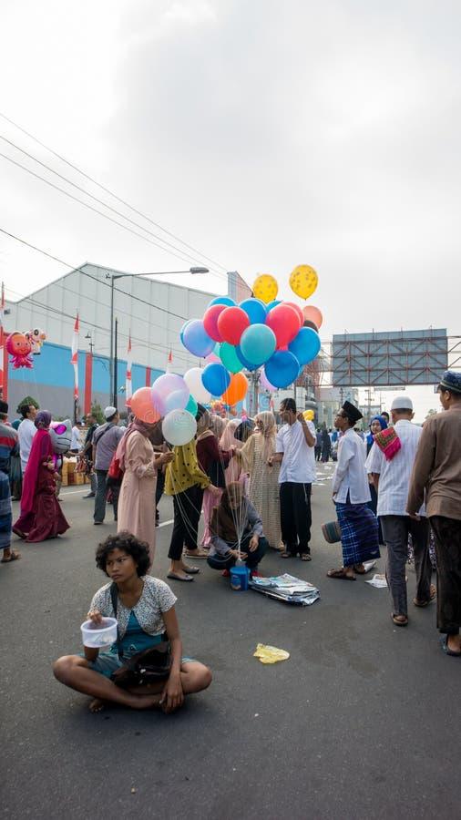 Żebrak i ludzie sprzedajemy balony latamy po Eid modlitwy w alun-alun mieście Blita zdjęcia royalty free