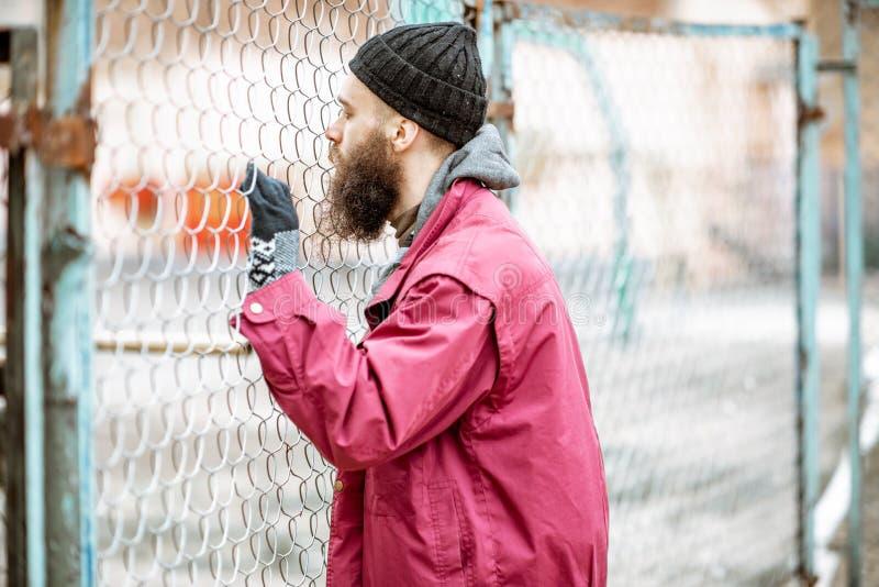 Żebrak lub więzień blisko starego metalu ogrodzenia outdoors zdjęcia stock
