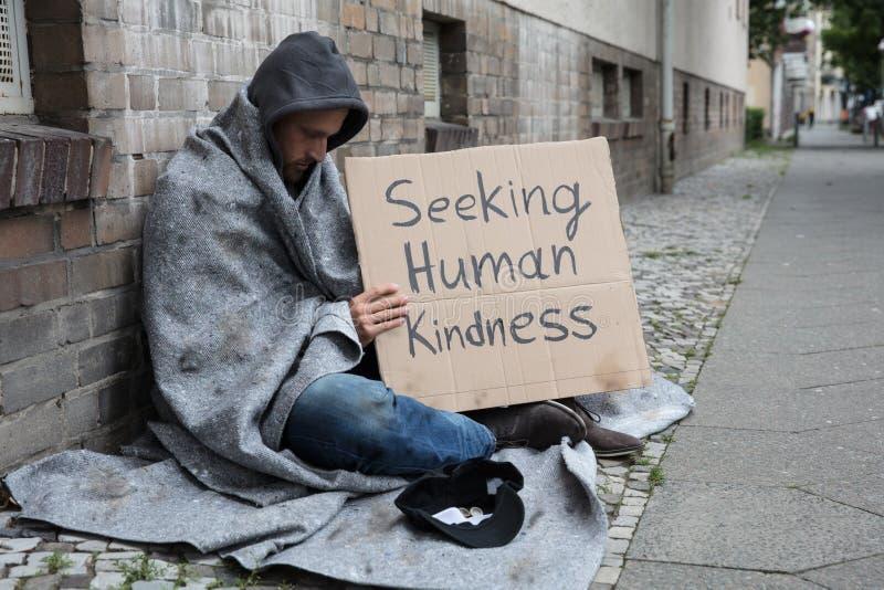 Żebrak Pokazuje Szukający Ludzkiej dobroci znaka Na kartonie zdjęcie royalty free