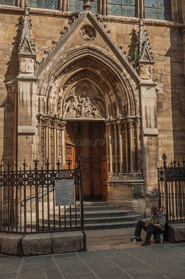 Żebrak przed gothic kościół na alei przy zmierzchem w Paryż obrazy stock