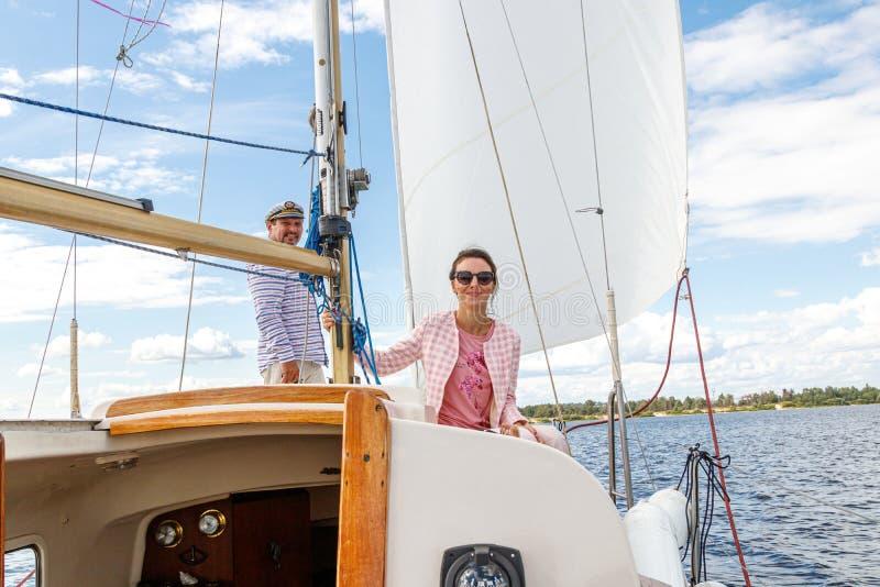Żeglarza mężczyzna w nakrętce z dziewczyną na łodzi pod żaglem przeciw wodzie i niebu zdjęcia stock