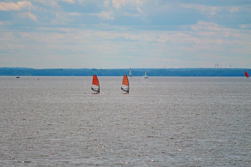 Żeglować deski z czerwonymi żaglami w morzu obrazy stock