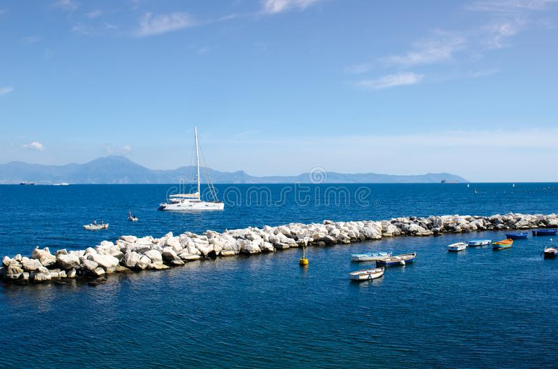 Żeglowania catamaran jachtu kłamstwa cumowali właśnie outside kamienny falowy łamacz w zatoce Naples, z Amalfi linią brzegową w b obraz stock