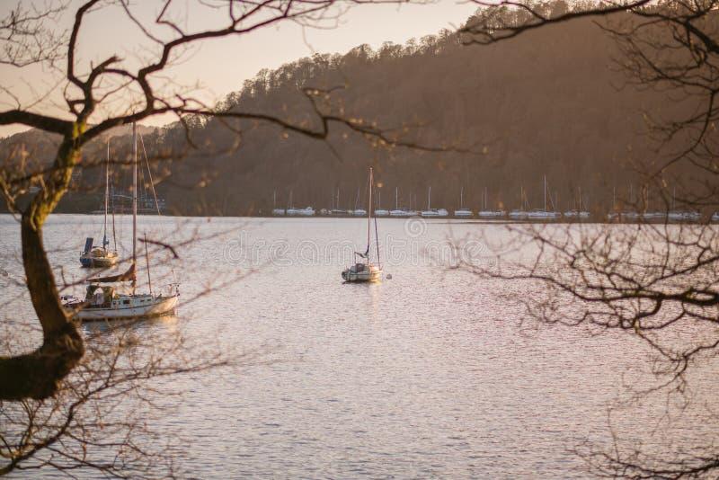 Żeglowanie łodzie siedzą stacjonarnego na Jeziornym Windermere podczas wczesnego wiosna zmierzchu - Jeziorny okręg, Cumbria - obraz royalty free