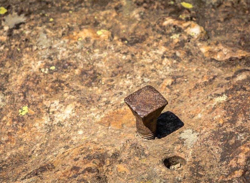 Żelazny gwóźdź w skale blisko z dziurą wyciągany gwóźdź zdjęcia royalty free