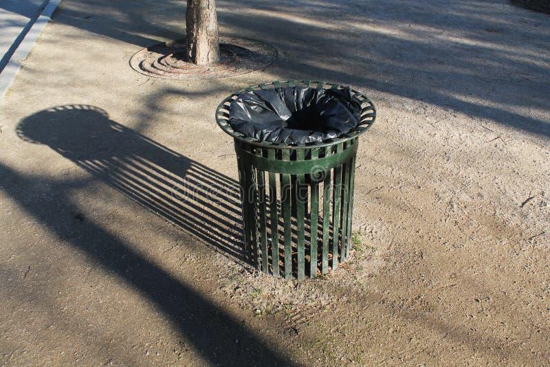 Żelazny kosz na śmieci z zieleń barami w parkowym kastingu elongated cień zdjęcie stock