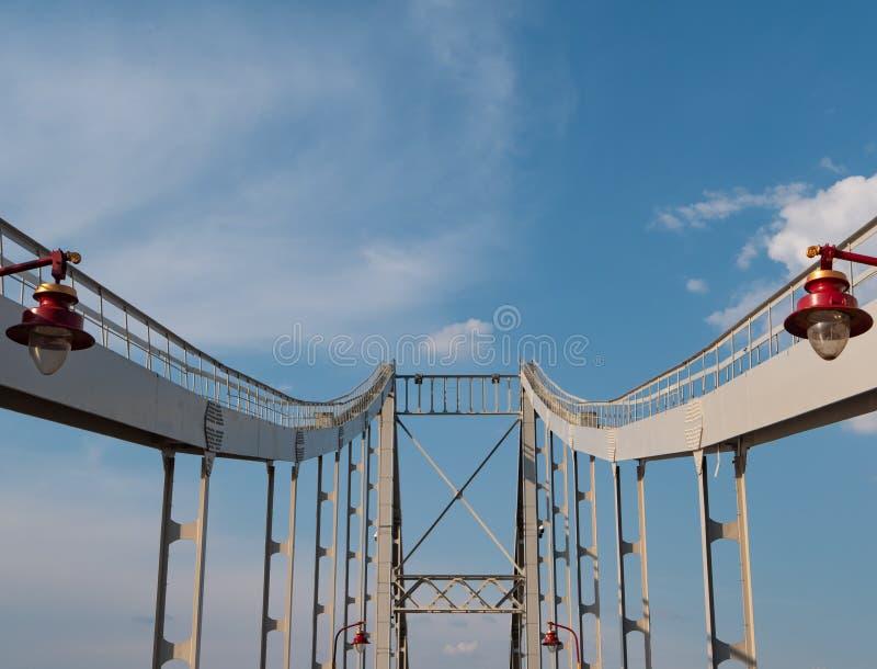 Żelazny most z czerwonymi nowożytnymi miasto lampionami głęboka perspektywa, bridżowe kolumny prowadzi niebieskie niebo na tle obraz royalty free