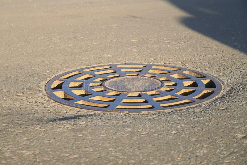 Żelazny round manhole kłama na bruku W mieście kanał ściekowy zamyka ląg zdjęcie stock