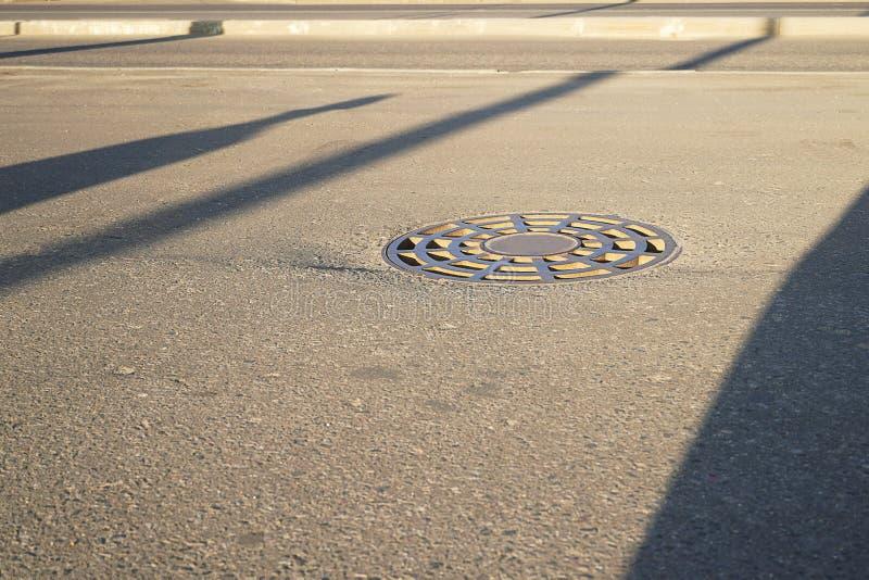 Żelazny round manhole kłama na bruku W mieście kanał ściekowy zamyka ląg sity fotografia royalty free