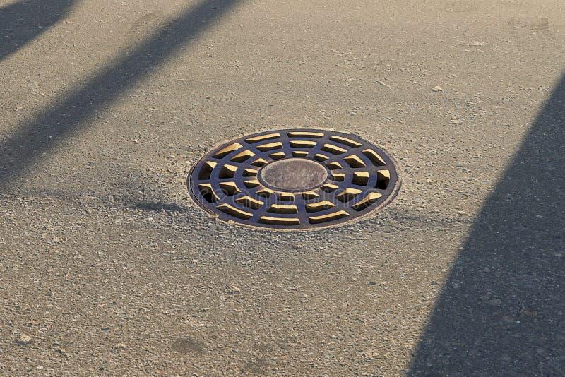 Żelazny round manhole kłama na bruku W mieście kanał ściekowy zamyka manhole pokrywą z dziurami zdjęcia stock