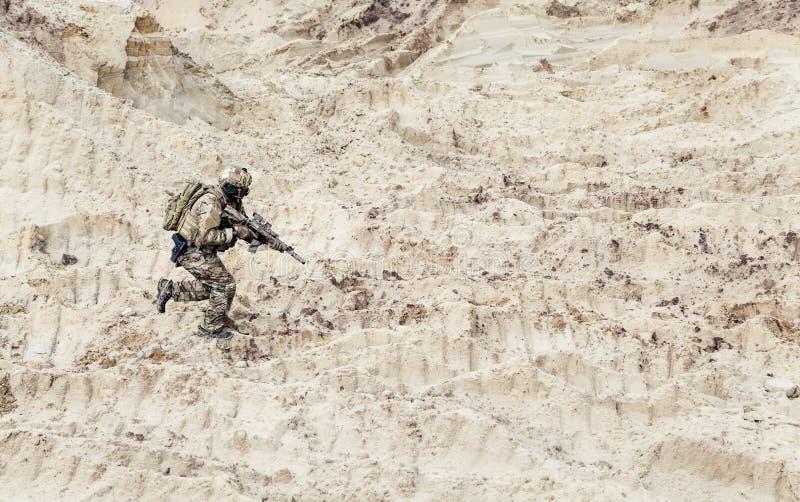 Żołnierz biega samotnie przez pustyni z karabinkiem obrazy royalty free