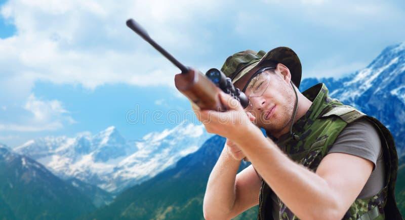 Żołnierz lub myśliwy z armatnim celowaniem lub strzelaniną fotografia stock