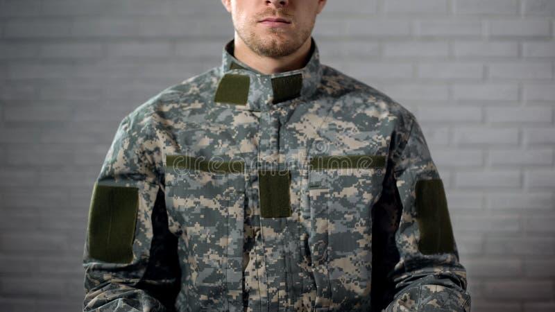 Żołnierz w kamuflażu obsiadaniu przeciw biel ścianie, służba wojskowa, szablon obraz royalty free