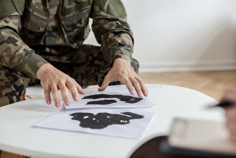 Żołnierz w zielonych Moro jednolitych wybiera obrazkach podczas terapii z psychiatra obraz royalty free