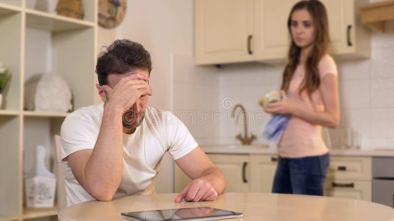 Żona łaja jej bezrobotnego męża przy kuchnią, chłosta on dla płonącego czasu obrazy stock