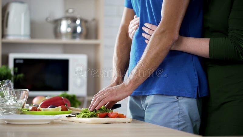 Żona delikatnie ściska jej męża który kulinarna jarzynowa sałatka dla rodzinnego lunchu fotografia royalty free