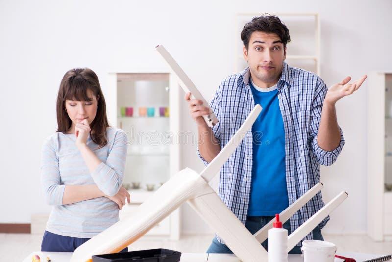 Żona pomaga mąż naprawa łamający krzesło w domu obrazy stock