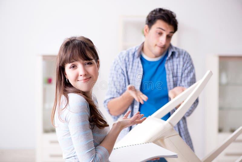 Żona pomaga mąż naprawa łamający krzesło w domu zdjęcie stock