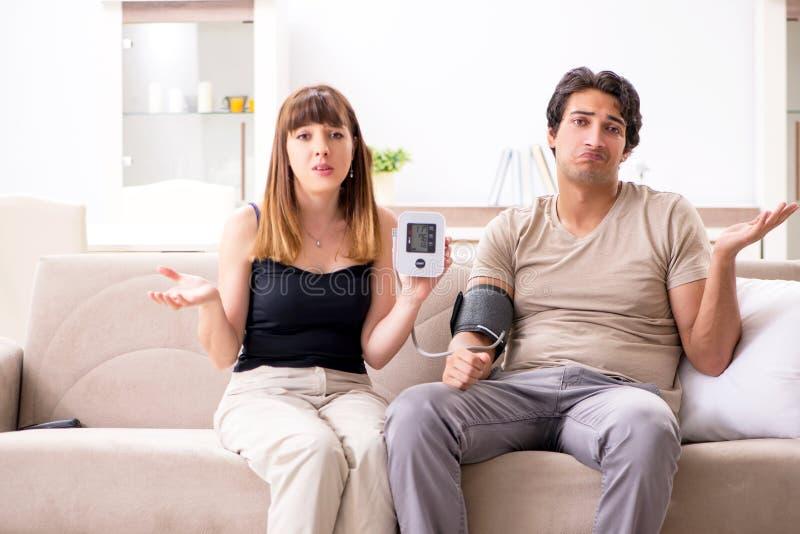 Żona sprawdza męża ciśnienie krwi obraz royalty free