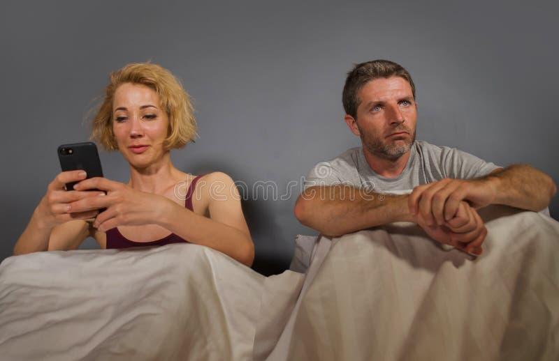 Żona używa telefon komórkowego w łóżku z jej gniewnym sfrustowanym mężem i mężczyzny uczuciem ignorował spęczenie i zanudzał w ko obraz stock