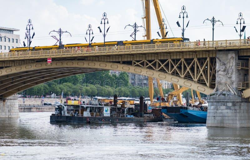 Żuraw i prac łodzie działa przy miejscem wypadek dokąd dwa łodzi one zderzali się pod Margaret mostem na rzecznym Danube zdjęcia royalty free