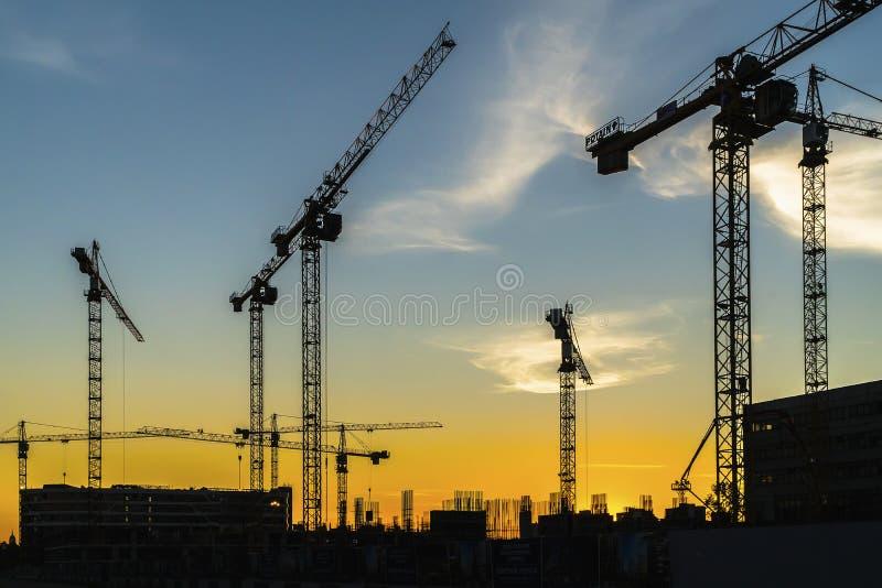 Żurawie pracuje na budowie lokalowa nieruchomość w poprzednim i obrazy stock