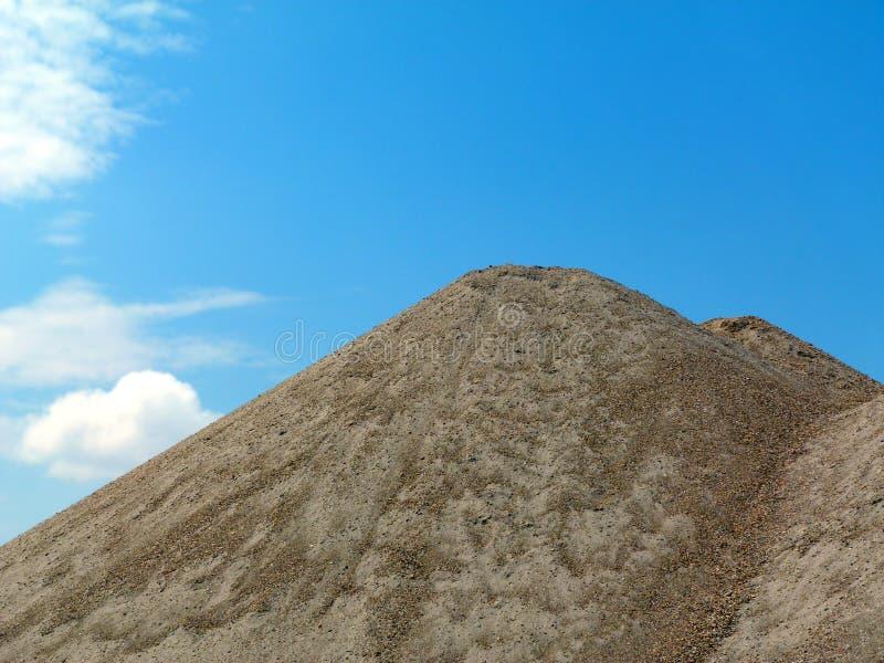 Żwir wypływa pod niebieskim niebem i białymi chmurami zdjęcie royalty free