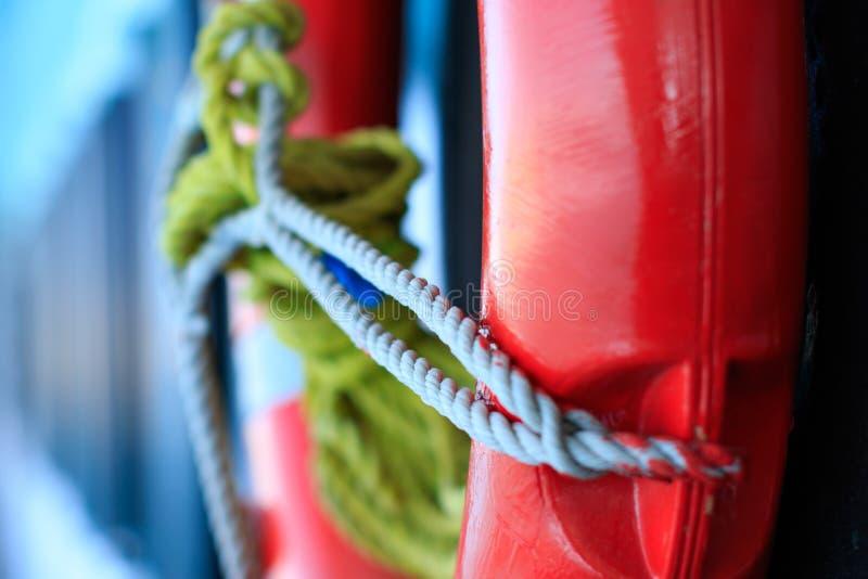 Życia boja w czerwonym kolorze z popielatym arkana kablem na dennej statek łodzi na zamazanym błękitnym tle, lifebuoy bezpiec fotografia royalty free