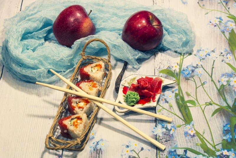 Życie Rolki w łozinowym koszu, jabłkach i pikantność na lekkim tle, obrazy royalty free