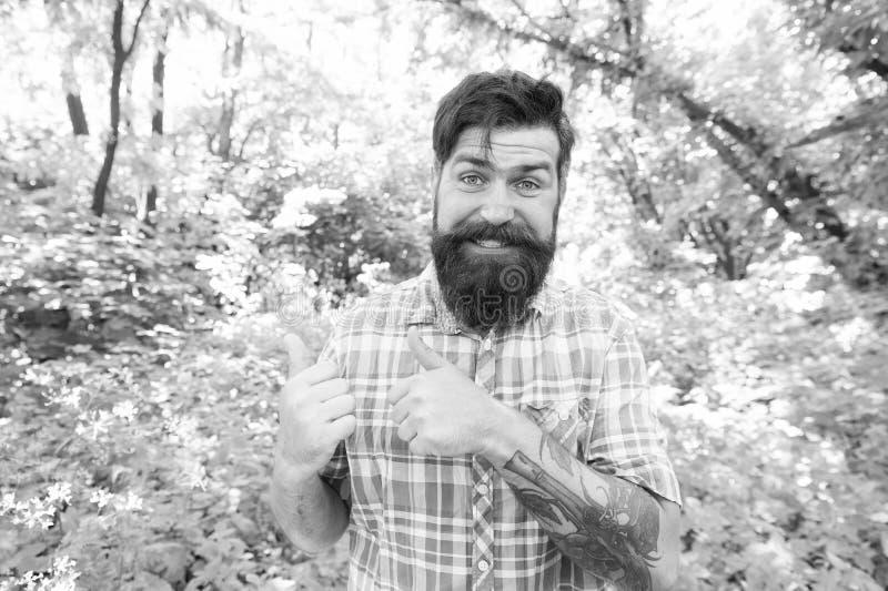 Życie w szczęśliwym życiu Szczęśliwy hipster, który daje kciuki gesty na naturalnym krajobrazie Emocjonalny facet z długimi wąsam zdjęcia stock
