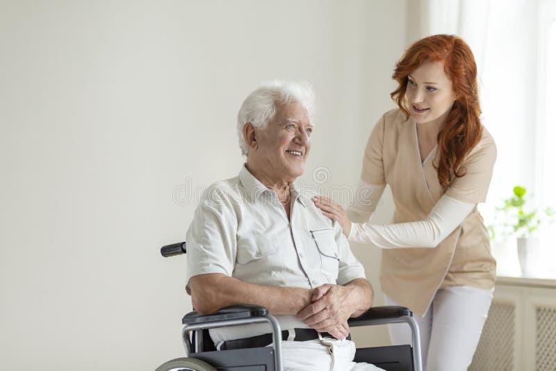 Życzliwa pielęgniarka wspiera uśmiechający się paraliżującego starszego mężczyzna w whee zdjęcia stock