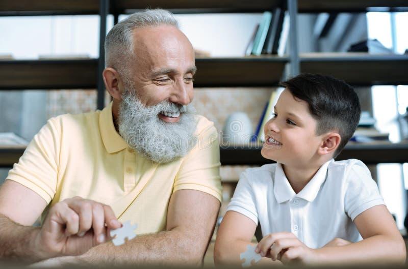 Życzliwe starsze osoby mężczyzna i wnuk bawić się wyrzynarki łamigłówkę zdjęcia stock