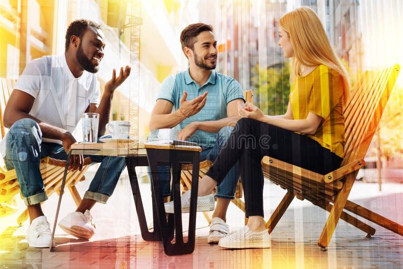 Życzliwi ucznie patrzeje ciekawiący podczas gdy pijący kawę i opowiadać zdjęcie stock