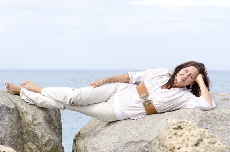 Życzliwy atrakcyjny dojrzały kobiety lying on the beach przy oceanem obrazy royalty free