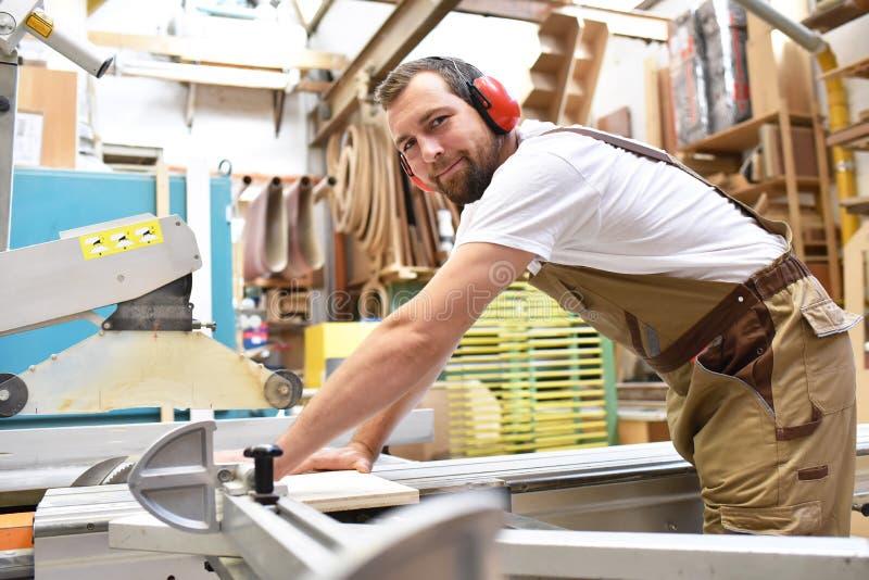 Życzliwy cieśla z uszatych ochraniaczów i pracujących ubrań worek zdjęcie royalty free