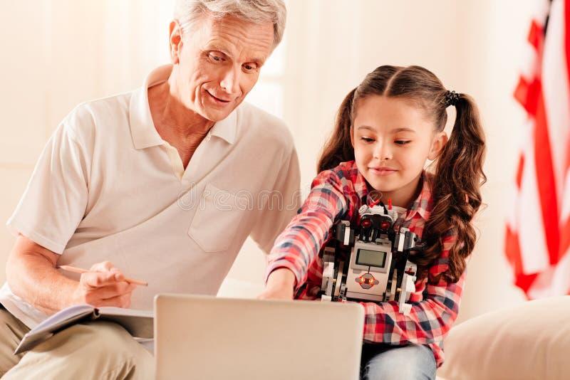 Życzliwy dziadek i dziewczyna opowiada o nowatorskich technologiach obraz royalty free