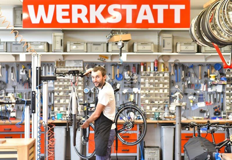 Życzliwy i kompetentny rowerowy mechanik w warsztacie naprawia a obraz royalty free