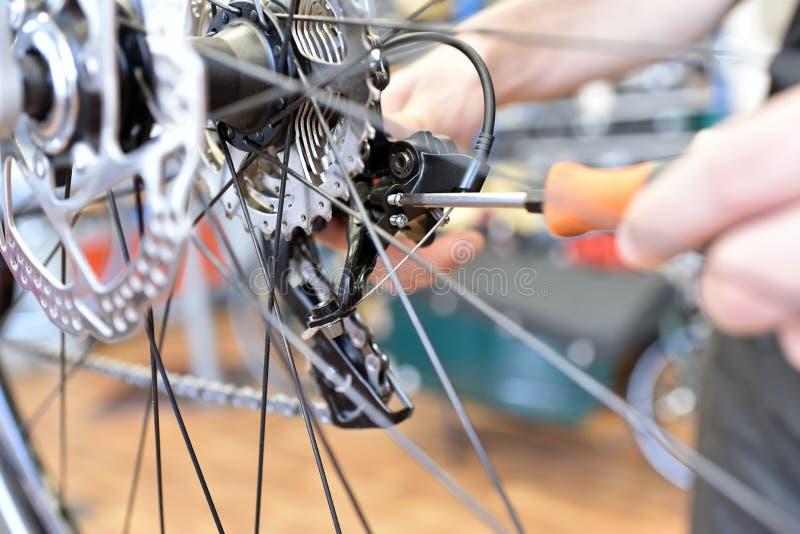 Życzliwy i kompetentny rowerowy mechanik w warsztacie naprawia rower zdjęcie stock