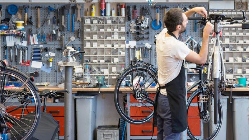 Życzliwy i kompetentny rowerowy mechanik w warsztacie naprawia rower obrazy royalty free