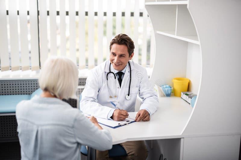 Życzliwy lekarz praktykujący ono uśmiecha się podczas gdy patrzejący pacjenta zdjęcia royalty free