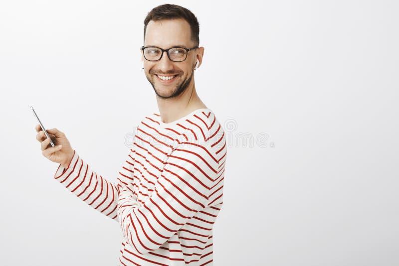 Życzliwy radosny dorosły coworker z szczecina, jest ubranym modnego czarnego eyewear i pasiastego pulower patrzeje prawy, i fotografia stock