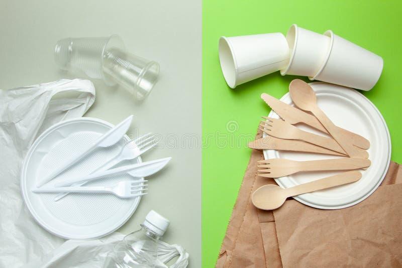 Życzliwy rozporządzalny tableware robić bambusowy drewno i papier na zielonym tle Plastikowi szkodliwi naczynia i cutlery obraz royalty free
