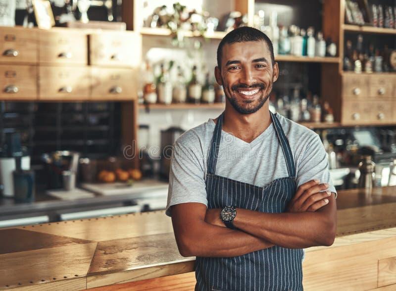 Życzliwy ufny męski właściciel przy jego kawiarnią zdjęcie royalty free